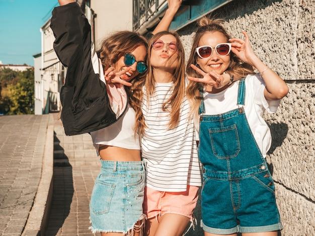 Portret van sexy zorgeloze vrouwen die zich voordeed op de straat achtergrond. positieve modellen plezier in zonnebril Gratis Foto