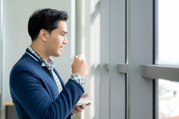 Portret van slimme en knappe jonge zakenman die een koffie drinken en buiten het venster dicht omhoog kijken. Premium Foto