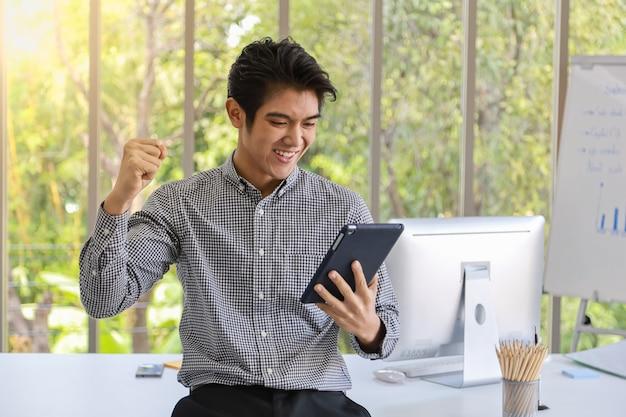 Portret van slimme jonge aziatische zakenmanholding tablet en het voelen van blije en opgeheven vuist in werkruimte met computer en vergaderingsraad en toebehoren op bureau. Premium Foto