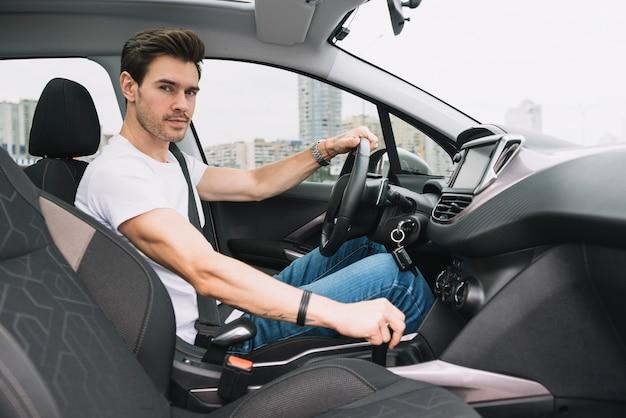 Portret van slimme jonge man zit in de auto rijden Gratis Foto