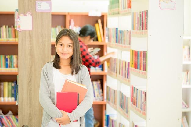 Portret van slimme student met open boek die het lezen in universiteitsbibliotheek Gratis Foto