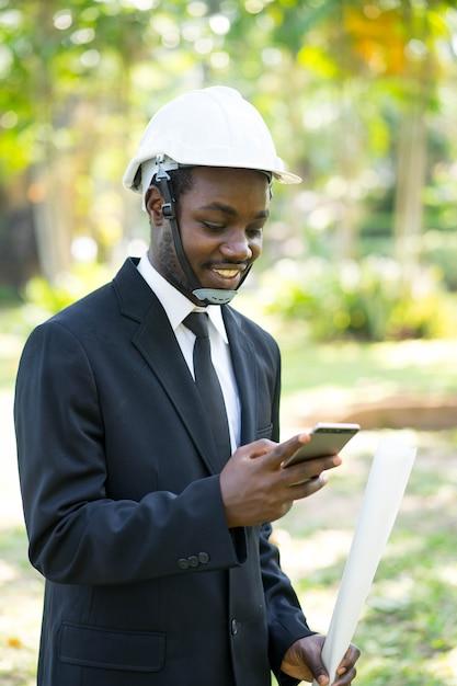 Portret van smile business afrikaanse man spelen smartphone met de natuur. Premium Foto