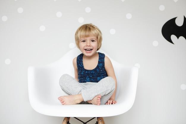 Portret van speelse peuter met blond haar die pyjama draagt, zittend op een stoel met gekruiste benen, lachend, mond wijd open, met zijn witte tanden, tegen een lege muur winnen Gratis Foto