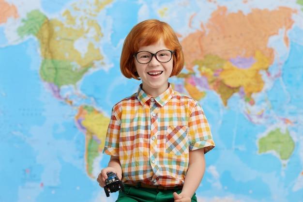 Portret van speelse roodharige jongetje in kleurrijke kleding, speelgoedauto in handen houden, met een goed humeur terwijl het gaan naar de kleuterschool. het grappige roodharigejongen stellen tegen wereldkaart. kinderen en school Gratis Foto