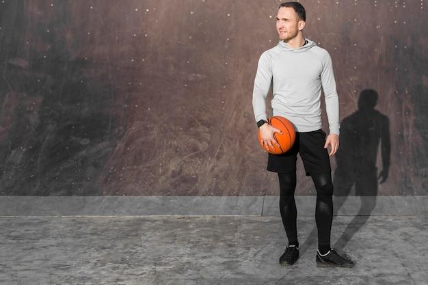 Portret van sportieve man met een basketbal Gratis Foto