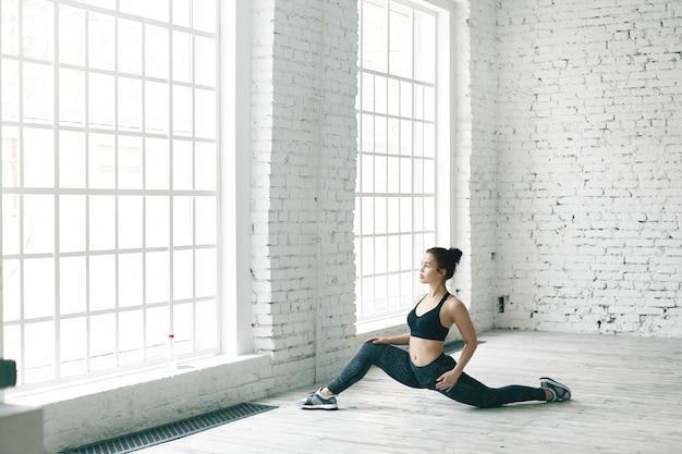 Portret van sterke flexibele jonge kaukasische sportvrouw in trendy sportuitrusting die zich uitrekken stelt stelt, zich voor voorsplitsingen voorbereidt. aantrekkelijk fit meisje doet oefeningen om de bekkengezondheid te versterken Gratis Foto
