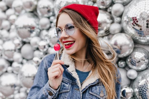 Portret van stijlvol meisje in denim jasje snoep eten en wegkijken. prachtige europese dame in rode hoed en ronde bril poseren met lolly op glanzende muur. Gratis Foto