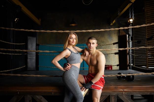 Portret van stijlvolle jonge man en vrouw met slanke gespierde lichamen poseren in de sportschool, buiten de boksring zitten, omarmen, kiezen voor een gezonde, actieve levensstijl. vechtsporten, sport en fitness concept Gratis Foto