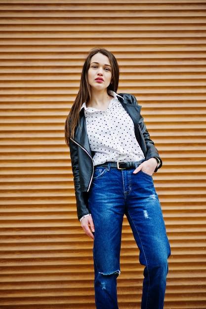 Portret van stijlvolle jonge vrouw die op leerjasje en gescheurde jeans in straten van stad draagt Premium Foto