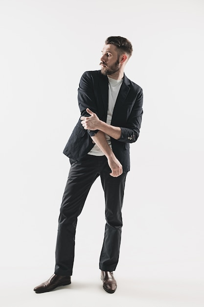 Portret van stijlvolle knappe jonge man die tegen wit. man met jas Gratis Foto