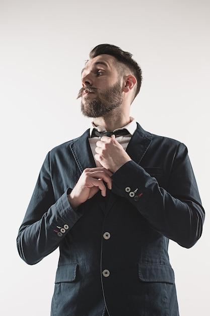 Portret van stijlvolle knappe jongeman permanent in studio tegen wit. man met jas Gratis Foto