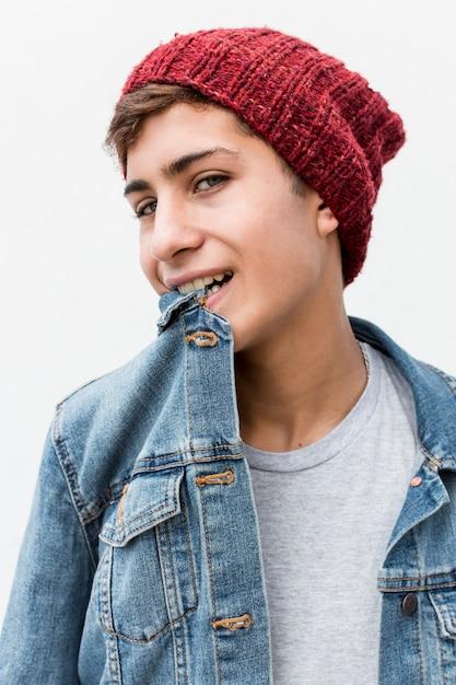 Portret van stijlvolle tiener met kraag van denim shirt in zijn mond tegen een witte achtergrond Gratis Foto