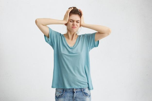Portret van stressvolle blonde vrouw in vrijetijdskleding met hoofdpijn hand in hand op haar hoofd fronsen haar gezicht met ontevreden blik. Gratis Foto
