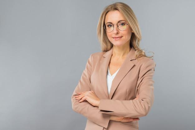 Portret van succesvolle blonde jonge vrouw met gekruiste wapens die zich tegen grijze achtergrond bevinden Gratis Foto