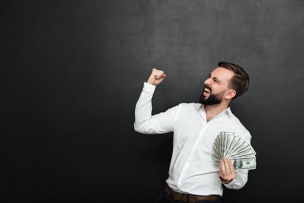 Portret van succesvolle man in wit shirt verheugend als winnaar met fan van 100 dollarbiljetten in de hand, balde vuist opzij over donkergrijs Gratis Foto