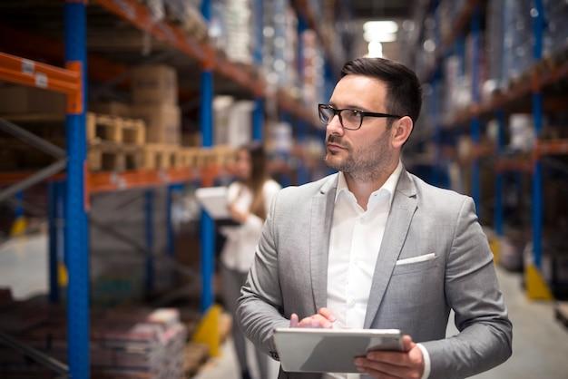 Portret van succesvolle zakenman manager ceo tablet houden en wandelen door magazijn opslagruimte op zoek naar planken Gratis Foto