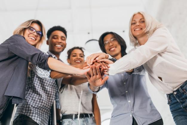 Portret van team van jonge kantoormedewerkers met hun handen in focus vervagen. binnenfoto van lachende internationale studenten in stijlvolle kleding die elkaar ondersteunen voor examens. Gratis Foto