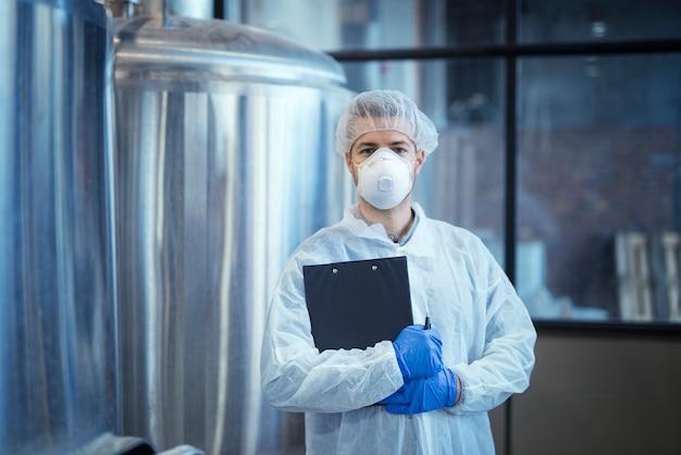 Portret van technoloog in wit uniform met haarnetje en beschermend masker en handschoenen permanent in farmaceutische of voedselfabriek met gekruiste armen Gratis Foto