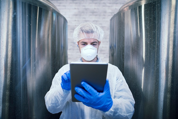 Portret van technoloog in witte beschermende uniforme tablet in voedselproductie fabriek Gratis Foto