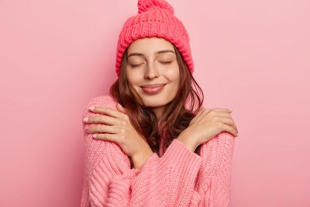 Portret van tevreden brunette vrouw knuffelt zichzelf, geniet van comfort in gebreide warme trui, houdt de ogen gesloten, koopt nieuwe winteroutfit, geïsoleerd op roze achtergrond. Gratis Foto