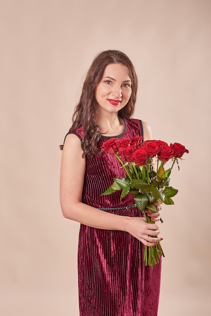 Portret van tevreden jonge vrouw in rode jurk met boeket rozen Premium Foto