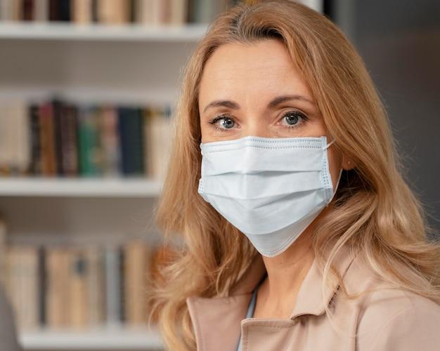 Portret van therapeut met masker in therapiekantoor Gratis Foto
