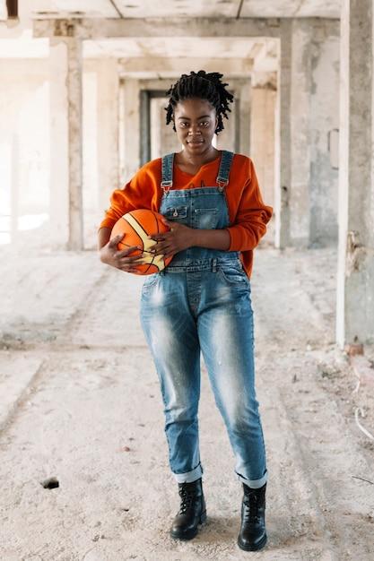 Portret van tiener het stellen met basketbalbal Gratis Foto