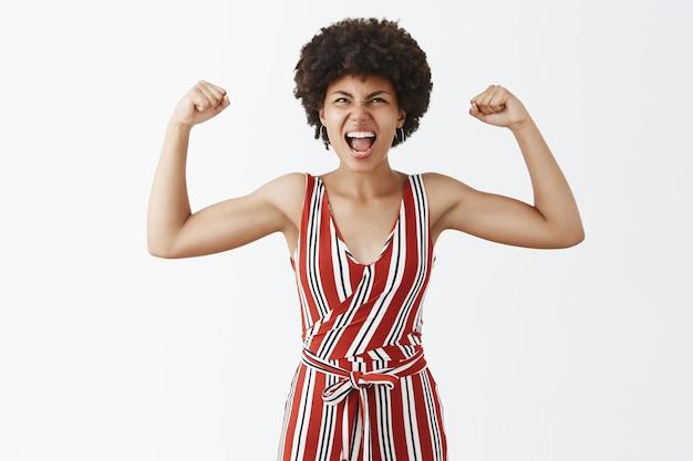 Portret van triomfantelijke vrolijke en expressieve knappe afro-amerikaanse sportvrouw in stijlvolle gestreepte overall die armen opheft om spieren te laten zien die schreeuwen van vreugde en opzoeken Gratis Foto