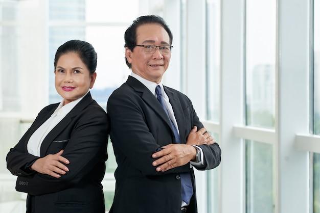 Portret van twee bedrijfsmensen die zich rijtjes bij het bureauvenster bevinden Gratis Foto