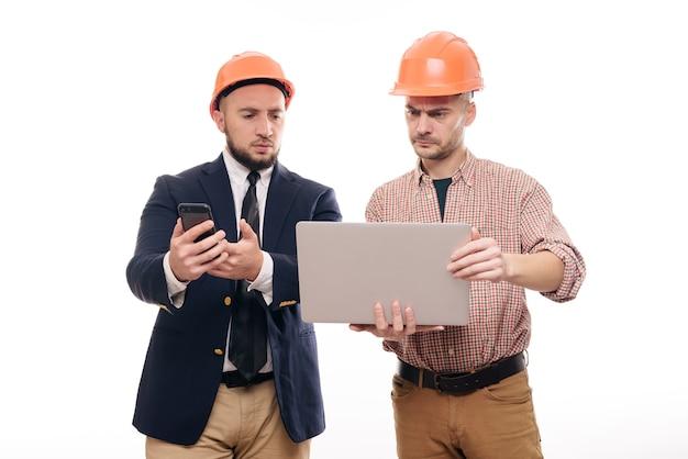 Portret van twee bouwers in beschermende oranje helmen die zich op wit geïsoleerde achtergrond bevinden en laptopvertoning bekijken. bespreek bouwproject Premium Foto