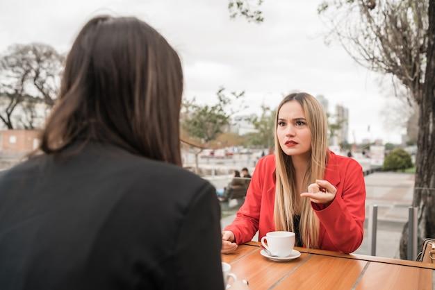 Portret van twee boze vrienden die een serieus gesprek hebben en bespreken terwijl ze in coffeeshop zitten. vriendschap concept. Premium Foto