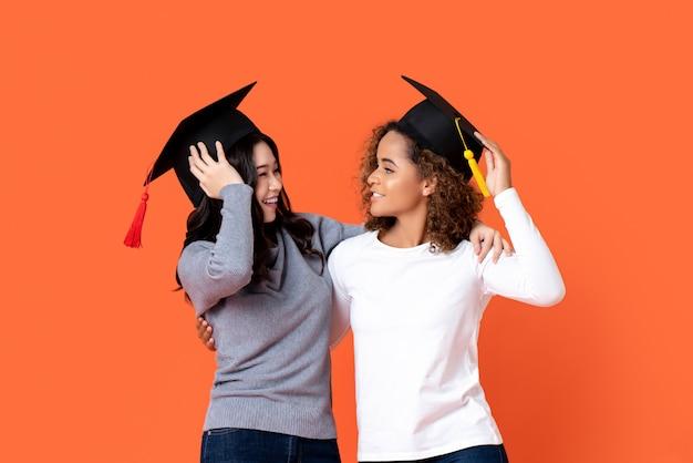 Portret van twee gelukkige gemengd ras vrouwen afstuderen bedrijf daar afstuderen caps kijken elkaar in oranje geïsoleerde muur Premium Foto