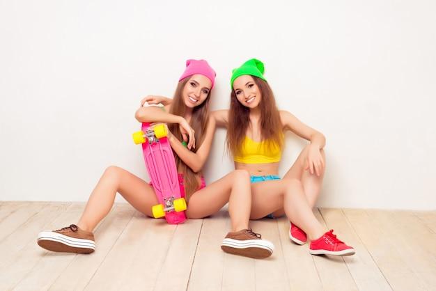 Portret van twee gelukkige stijlvolle meisjes aanbrengen op de vloer met skate Premium Foto