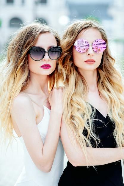 Portret van twee jonge aantrekkelijke tweelingzusjes in zonnebril op een stad in zwart-witte jurk Premium Foto