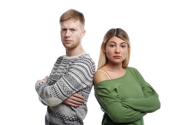 Portret van twee jonge mannelijke en vrouwelijke ouders van kaukasisch uiterlijk staan met gevouwen armen, boos kijken, ontevreden over het slechte gedrag van hun zoontje Gratis Foto