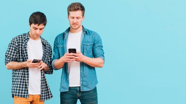 Portret van twee jonge mannen die zich tegen blauwe achtergrond bevinden die mobiele telefoon met behulp van Gratis Foto