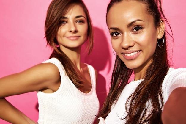 Portret van twee jonge modieuze glimlachende donkerbruine vrouwen. vrouwen gekleed in zomer hipster kleding. positieve modellen die selfie op telefoon op roze muur maken Gratis Foto