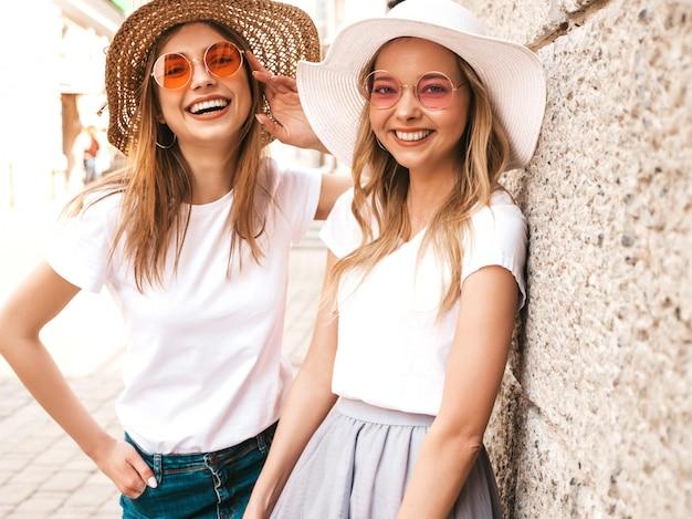 Portret van twee jonge mooie blonde glimlachende hipster meisjes in kleren van de trendy de zomer witte t-shirt. Gratis Foto
