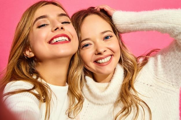 Portret van twee jonge stijlvolle glimlachende blonde vrouwen Gratis Foto