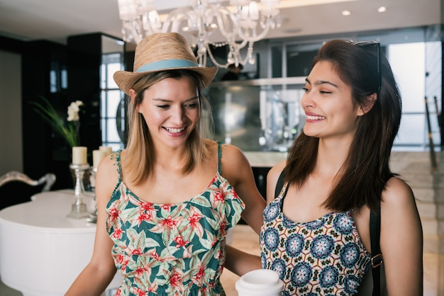 Portret van twee jonge vrienden die bij hotel aankomen en door lobby met hun bagage lopen. reis- en levensstijlconcept. Gratis Foto