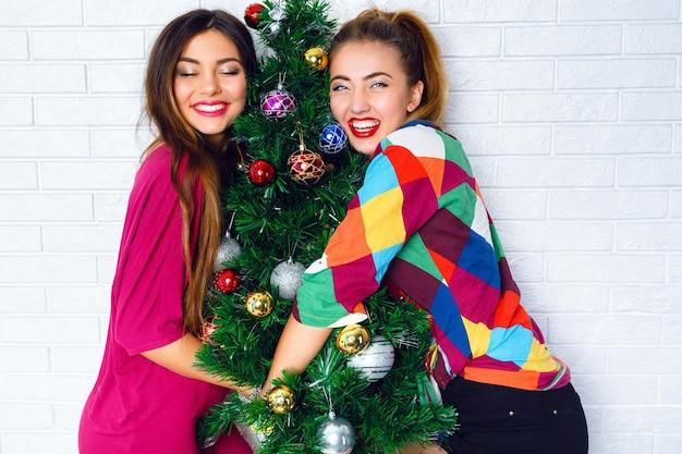 Portret van twee jonge vrouwen die een kerstboom omhelzen Gratis Foto