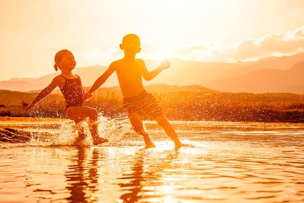 Portret van twee kinderen van 3 en 6 jaar die in de zee spelen en water om hen heen spuiten. Premium Foto
