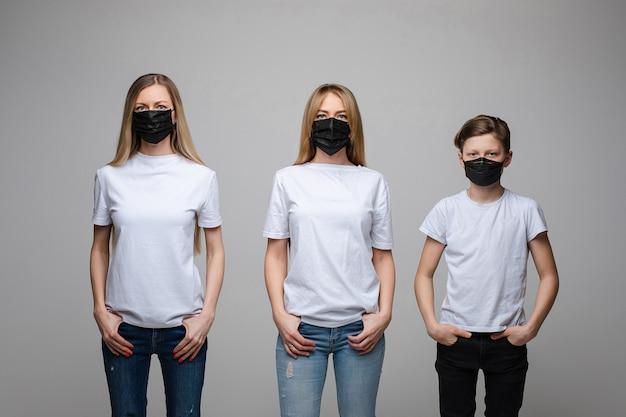Portret van twee knappe meisjes met lang blond haar en een jonge jongen met zwarte medische maskers op hun gezichten die op grijze achtergrond worden geïsoleerd Gratis Foto
