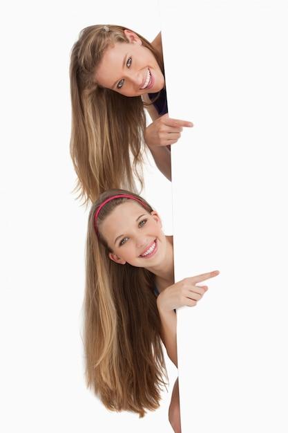 Portret van twee lange haarstudenten die achter een leeg teken richten Premium Foto