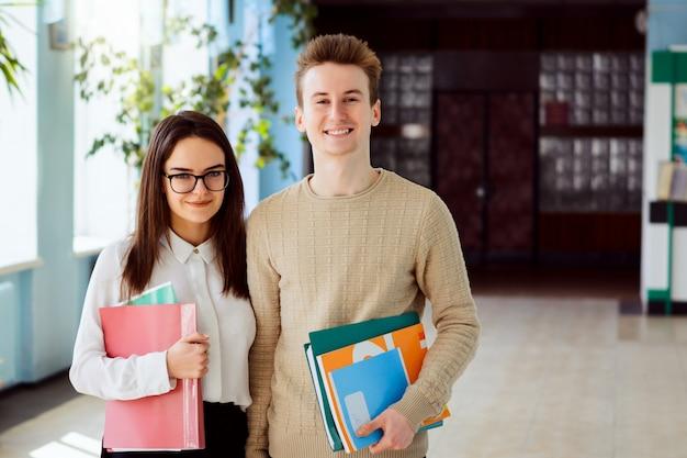 Portret van twee middelbare schoolstudenten met cursusboeken, handboeken en omslagen vóór klassen in schoolgang in zonnige dag Premium Foto