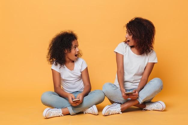 Portret van twee vrolijke afro-amerikaanse zusters Gratis Foto