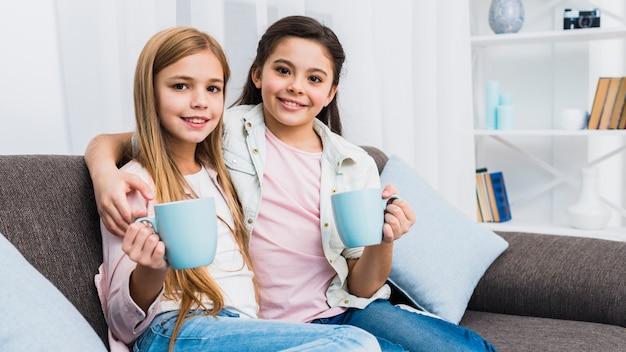 Portret van twee vrouwelijke kinderen samen zitten op de koffiemokken van de bankholding in de hand Gratis Foto