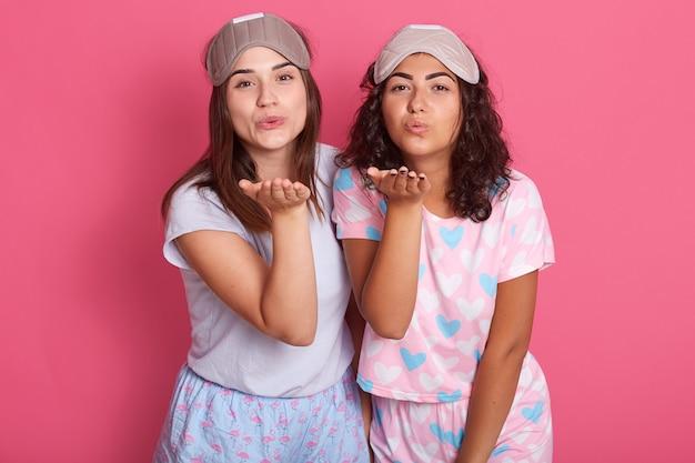 Portret van twee vrouwtjes die handen opheffen, een kus sturen, naar bed gaan, een pyjama dragen en een slaapmasker dragen Gratis Foto