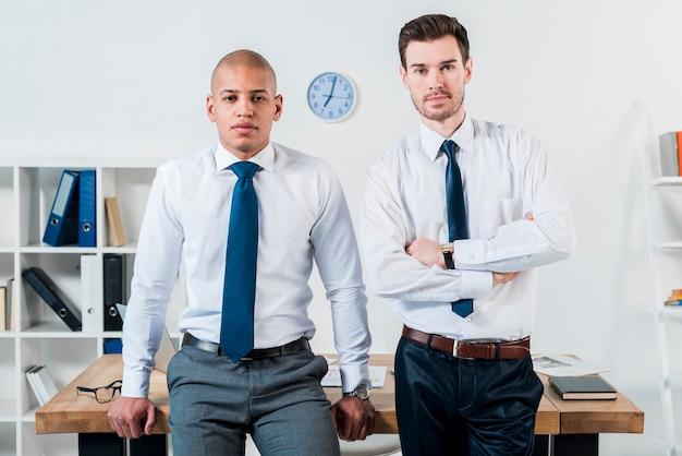 Portret van twee zekere jonge zakenman die zich voor bureau op kantoor bevinden Gratis Foto