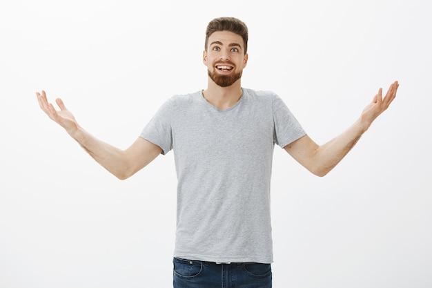 Portret van verbaasd en opgewonden verrast europese man met baard en handen in de lucht op zoek vreugdevol en dankbaar god te danken voor het helpen vervullen van verlangens en dromen over grijze muur Gratis Foto